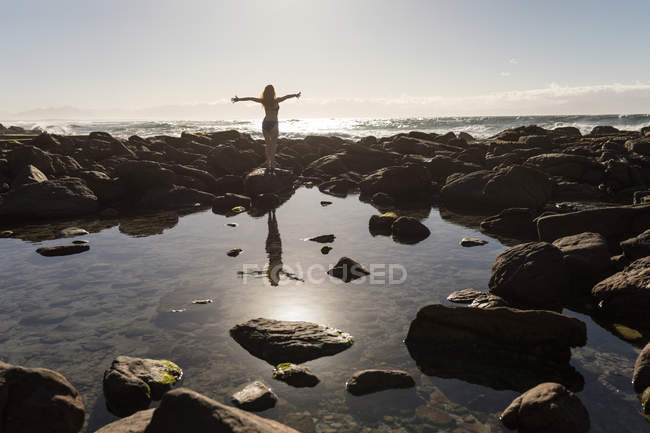 Vista posteriore della donna in piedi con le braccia distese sulle rocce — Foto stock