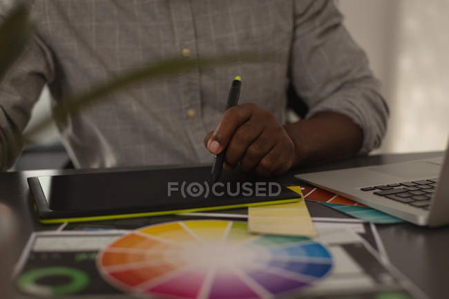 Sección media del diseñador gráfico senior que utiliza la tableta gráfica en la oficina - foto de stock