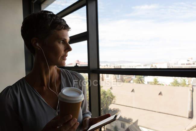 Зрілі підприємець прослуховування музики на навушники біля вікна офісу — стокове фото