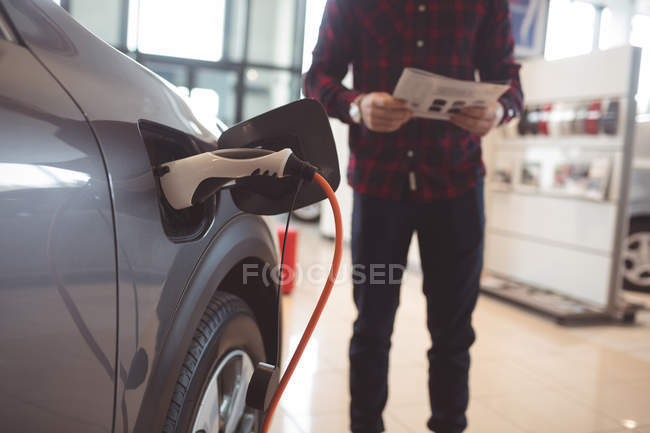 Fuel being filled in car tank at showroom — Stock Photo