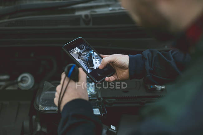 Mechanic taking picture of car engine with mobile phone in repair garage — Stock Photo