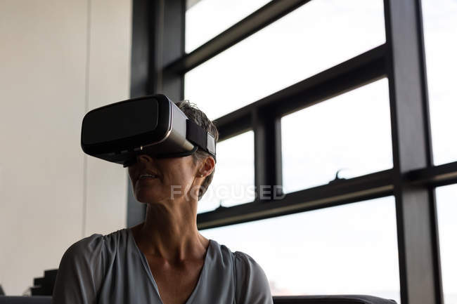 Mature businesswoman using virtual reality headset in the office — Stock Photo