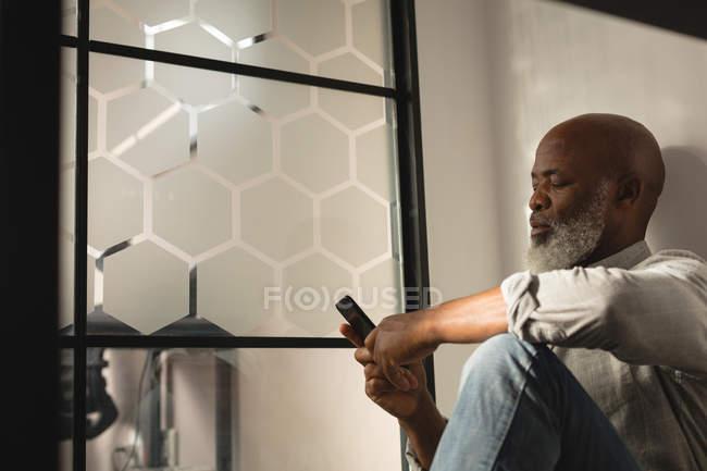 Disegnatrice Grafica Senior con il cellulare in ufficio — Foto stock