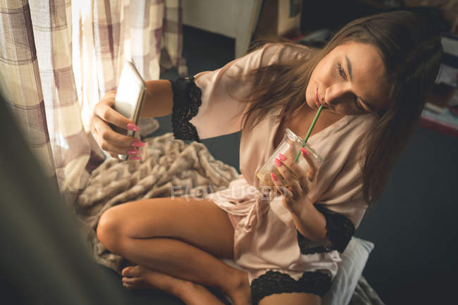 Mulher tomando selfie com telefone celular enquanto toma café frio em casa — Fotografia de Stock