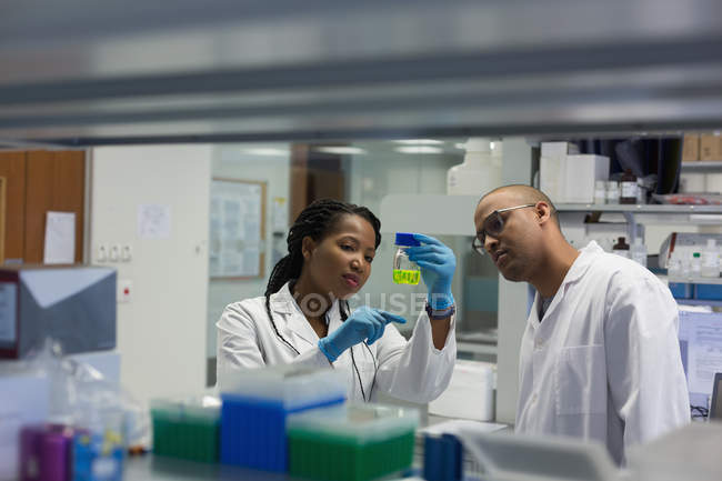 Scientists checking a solution in bottle in lab — Stock Photo