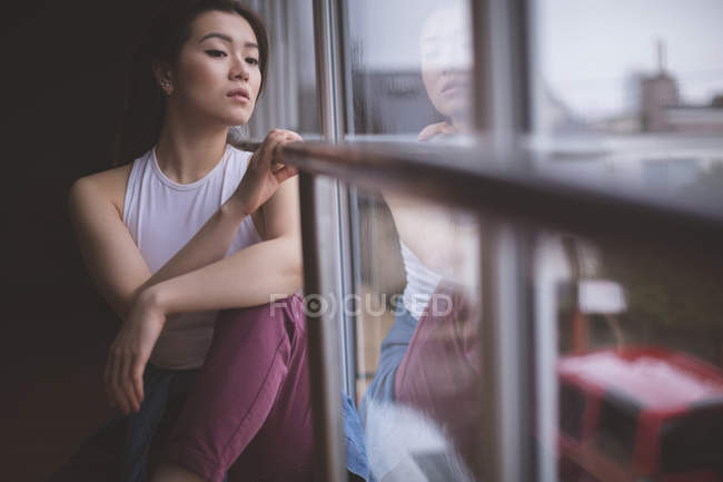Ragionevole ballerina che guarda attraverso la finestra in studio di danza — Foto stock