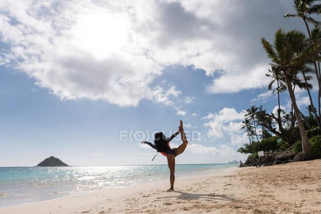 Femme exerçant à la plage par une journée ensoleillée — Photo de stock