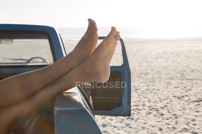 Frau entspannt sich mit den Füßen im Pickup am Strand — Stockfoto