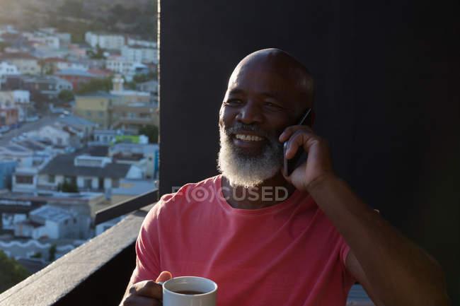 Homme âgé prenant un café tout en parlant sur un téléphone portable à la maison — Photo de stock