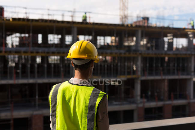 Rear view of female architect standing at construction site — Stock Photo