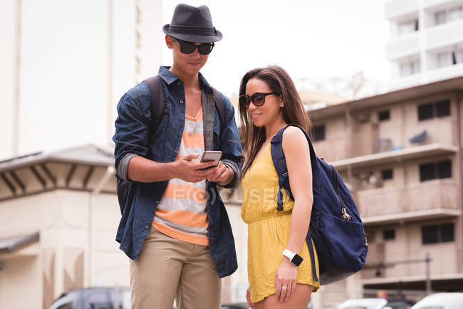 Couple reviewing pictures on mobile phone in the city — Stock Photo