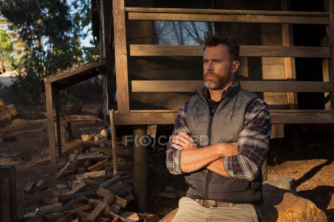 Thoughtful man sitting with arms crossed on rock in forest — Stock Photo