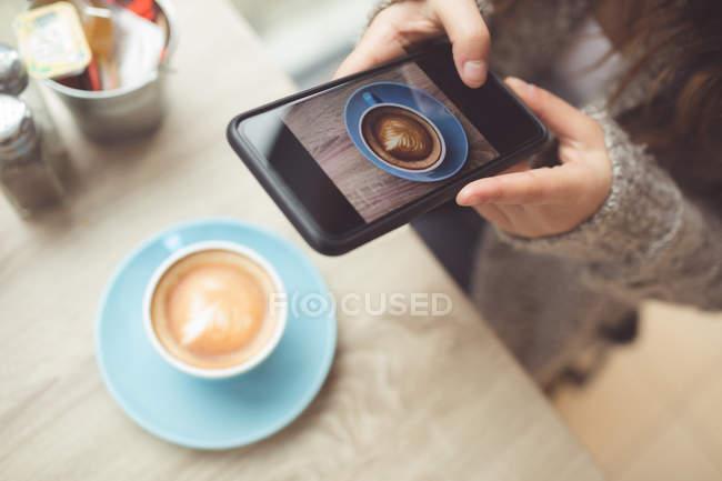 Donna cliccando foto di caffè con cellulare in caffetteria — Foto stock