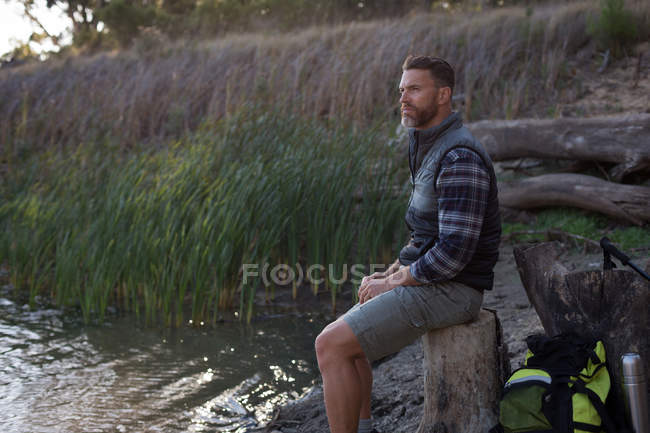 Side view of man relaxing on tree stump near river bank — Stock Photo