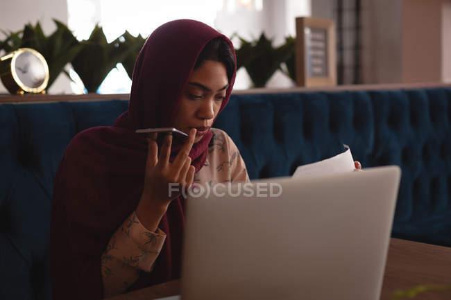 Деловая женщина в хиджабе разговаривает по мобильному телефону в офисной столовой — стоковое фото