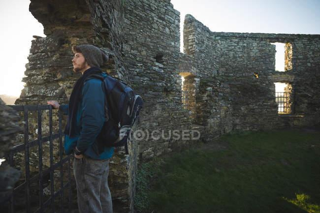 Молодой турист, стоящий в старых руинах в сельской местности — стоковое фото