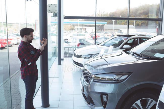 Продавец фотографирует машину с мобильного телефона в выставочном зале — стоковое фото