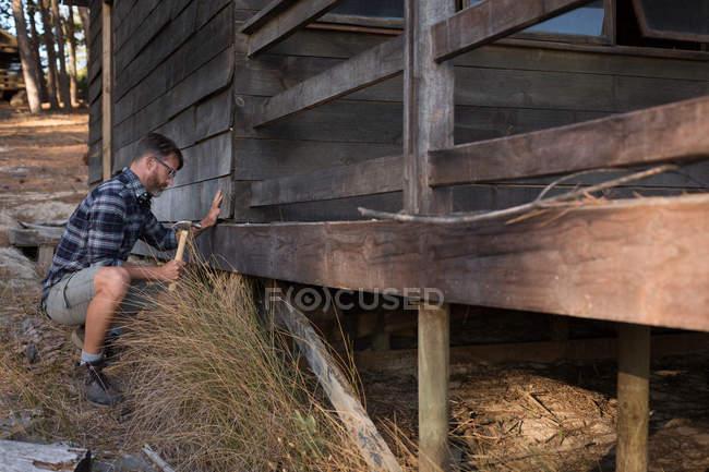 Uomo martellante assi di legno con martello in una giornata di sole — Foto stock