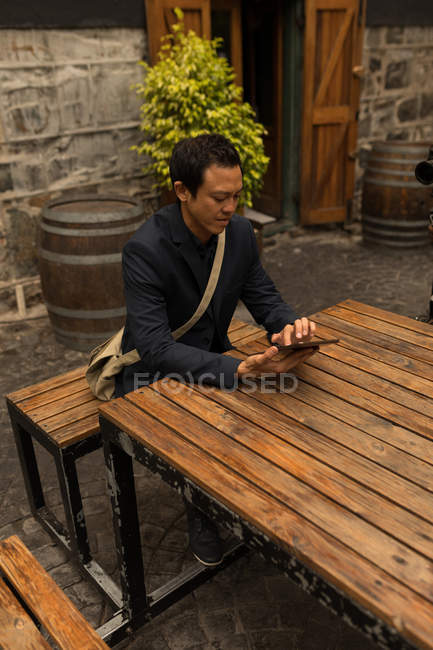Businessman using digital tablet in the pavement cafe — Stock Photo