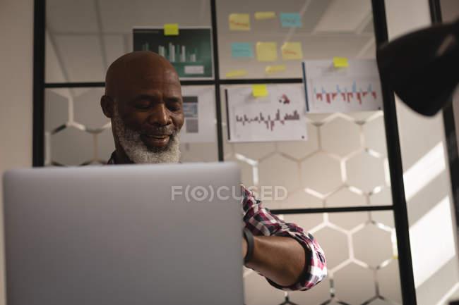 Senior graphic designer using laptop at desk in office — Stock Photo
