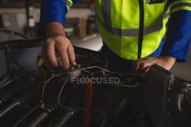 Engineer repairing aircraft engine in hangar — Stock Photo