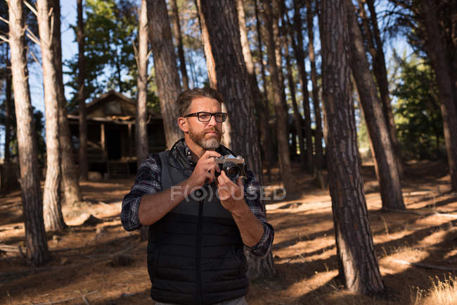Man ready to click photo of nature with camera in forest — Stock Photo
