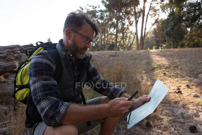 Side view of man looking at map in forest — Stock Photo