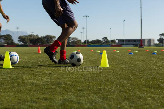 Футболіста дриблінг м'яч через шишки на спортивній ниві — стокове фото