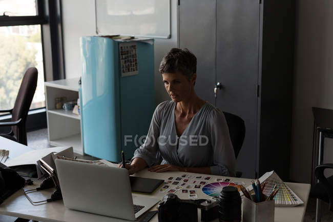 Graphic designer using graphic tablet at desk in the office — Stock Photo