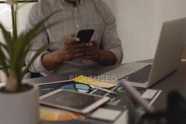 Sezione centrale del grafico senior utilizzando il telefono cellulare in ufficio — Foto stock