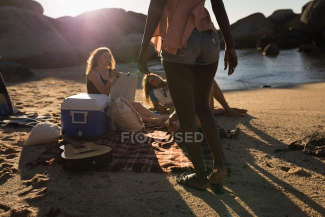 Amici femminili che hanno divertimento in spiaggia in una giornata di sole — Foto stock