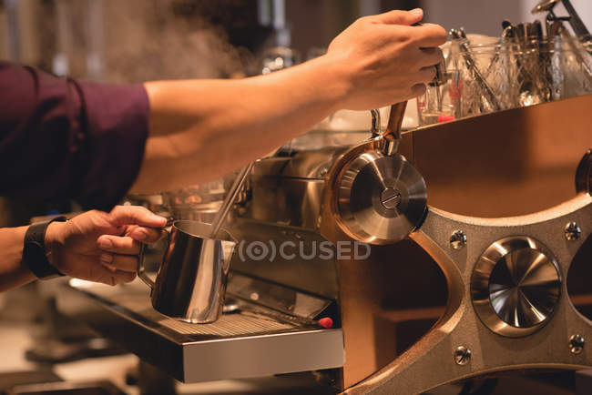 Mid section of waiter preparing coffee in coffee shop — Stock Photo