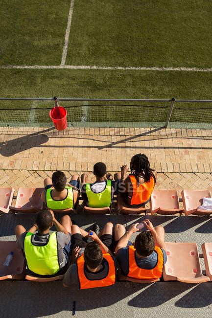 Висока кут зору футболістів розслабляючий на землянці — стокове фото