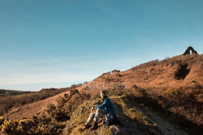 Männliche Wanderer entspannen sich an einem sonnigen Tag auf dem Land — Stockfoto