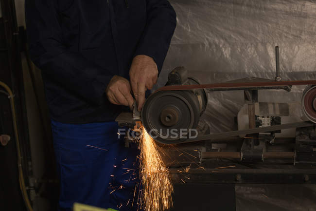 Worker shaping metal on machine in aircraft hangar — Stock Photo