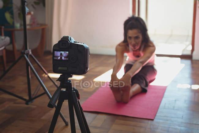 Женщина видео блоггер запись видео видеоблог во время тренировки на дому — стоковое фото