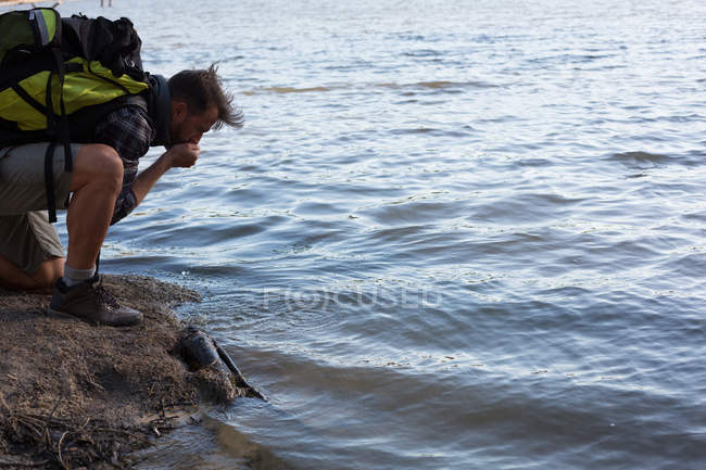 Side view of male hiker drinking water from river — Stock Photo