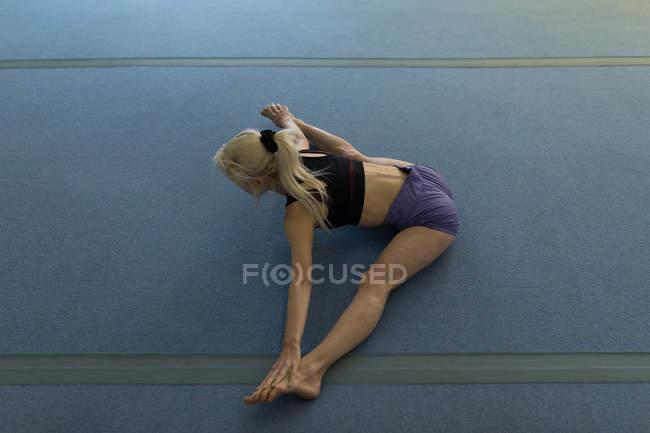 Sportive en effectuant l'exercice d'étirement au studio de remise en forme — Photo de stock