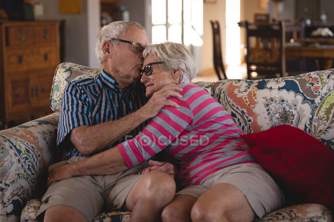 Romanced senior couple sitting on sofa at home — Stock Photo
