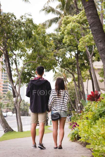 Rückansicht eines Paares, das gemeinsam auf dem Bürgersteig in der Stadt läuft — Stockfoto