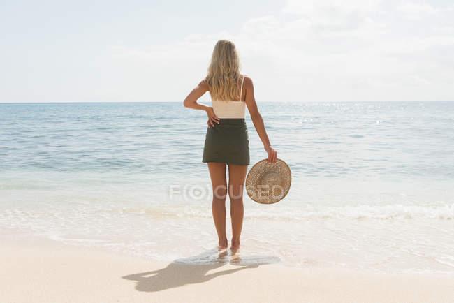 Vista traseira da mulher segurando o chapéu na praia — Fotografia de Stock