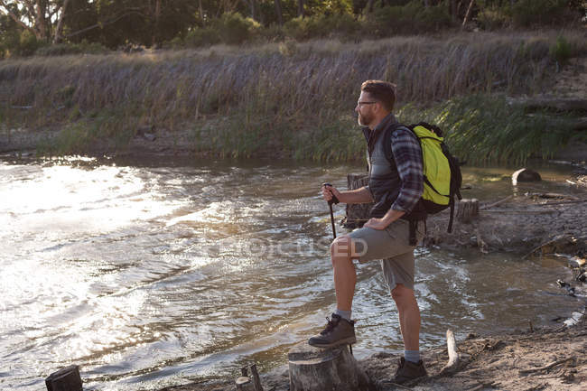 Side view of hiker looking at view near river bank — Stock Photo
