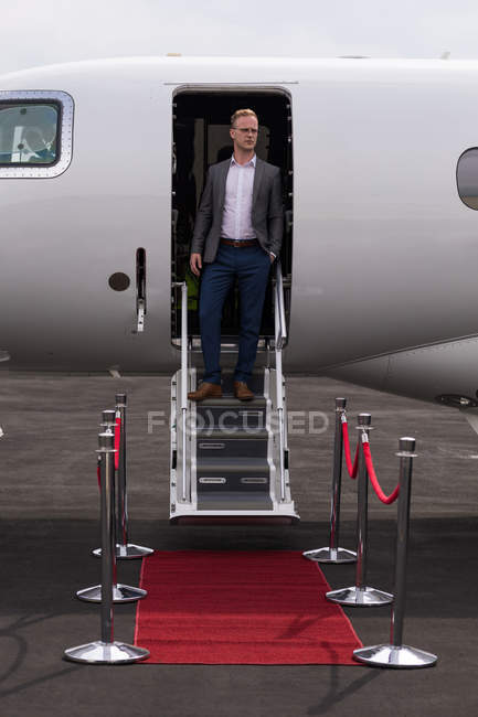 Businessman standing at the entrance of private jet at terminal — Stock Photo