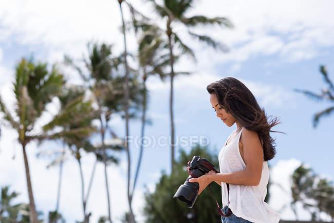 Jovem mulher, revendo fotos na câmera digital na praia — Fotografia de Stock