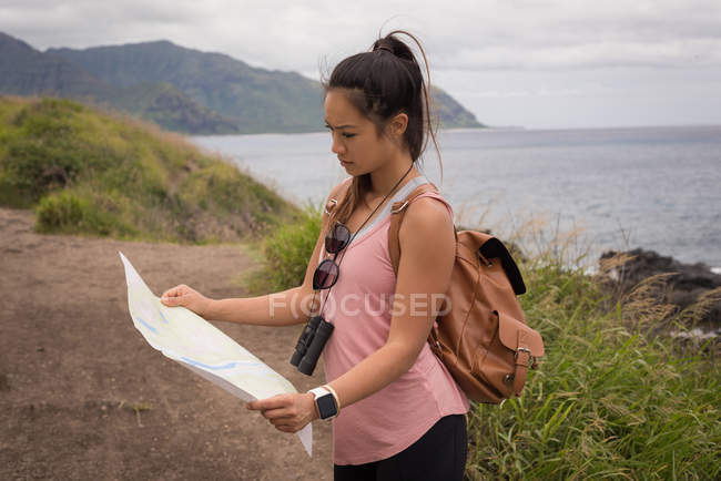 Beautiful woman looking at map in countryside — Stock Photo