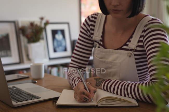 Розділ середині жінка писати щоденник вдома — стокове фото