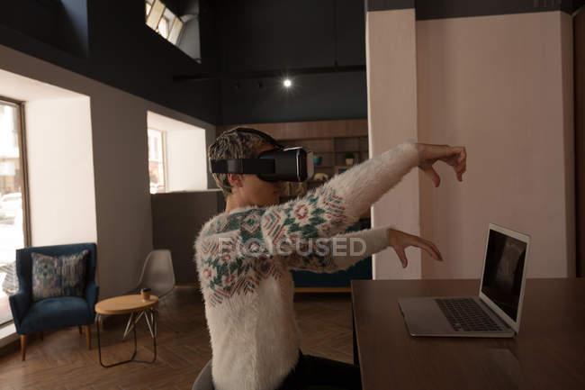 Бізнес-леді за допомогою віртуальної реальності гарнітуру в кафетерії в офісі — стокове фото