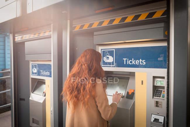 Жінка за допомогою автоматичного автомат на залізничному вокзалі — стокове фото