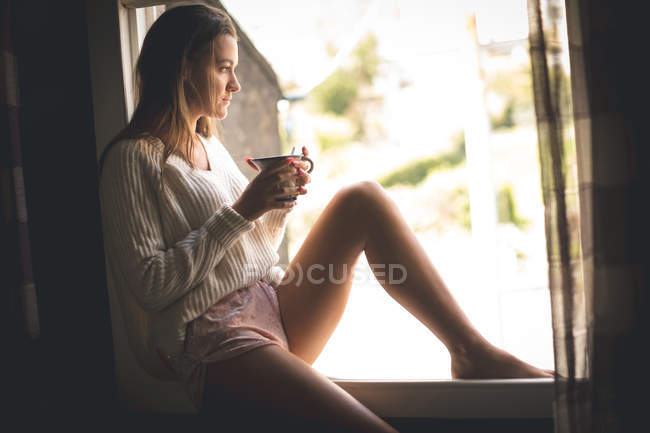 Thoughtful woman having coffee near window at home — Stock Photo