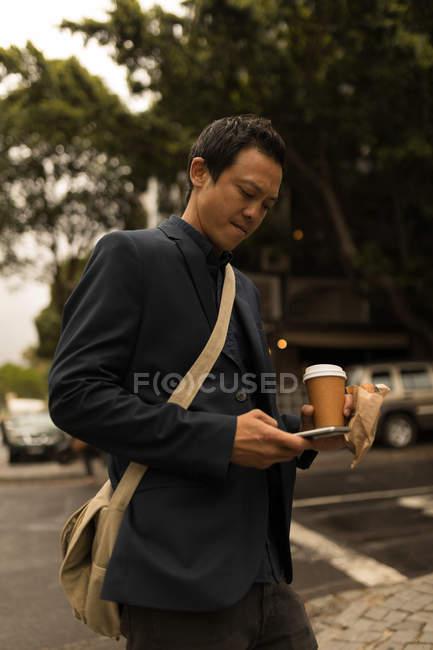 Бизнесмен с помощью мобильного телефона на улице — стоковое фото